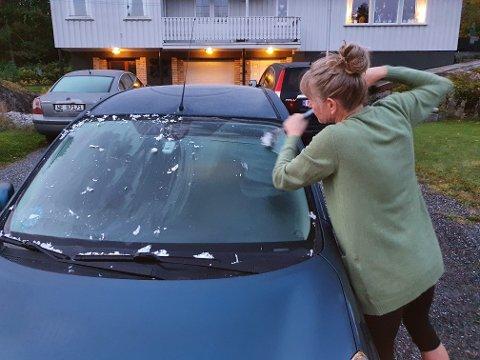 FROSTNATT: Kristin Holte måtte ut og skrape frontruta på bilen torsdag morgen etter høstens første frostnatt i distriktet.