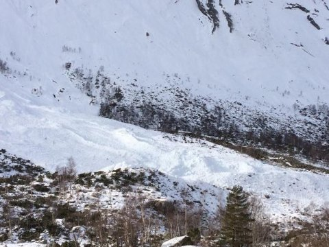 Snøraset i Ulvanoso like ved tunet i Friheim er godt synleg i landskapet. Store snømassar ligg på elvekanten.
