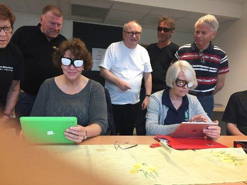 Synskontaktene prøver seg på nettbrett med briller som indikerer en synshemning mens medlemmer av Blindeforbundet følger med.