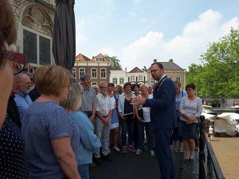 Blandakoret blir mottatt av borgermesteren på balkongen på det gamle rådhuset