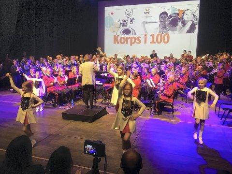 KORPS I 100: Ordfører Kari Anne Sand dirigerer felleskorpset. Drilljenter fra Kongsgårdmoen skolekorps i forgrunnen.