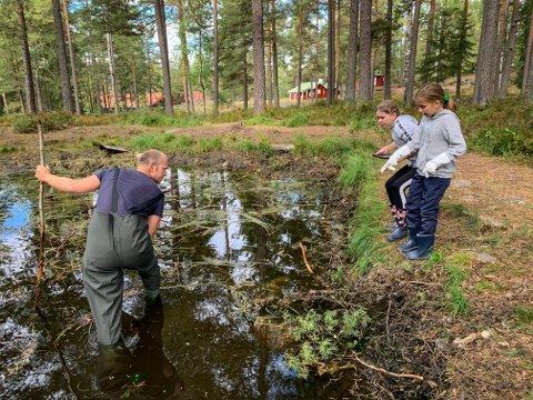 RYDDER: Elevene ved sjettetrinn på Gamlegrendåsen skole ryddet i den lille dammen på skoleområdet. Lærer Tommy A. Støa vasset ut i dammen og fant søppel, som elevene ryddet bort.