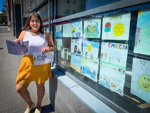 VIL GJERNE HA FLERE TEGNINGER: Lp-journalist Natalia C. Heinrich viser fram to av vinnertegningene. I vinduet til Lp henger det nå flere og flere flotte tegninger.