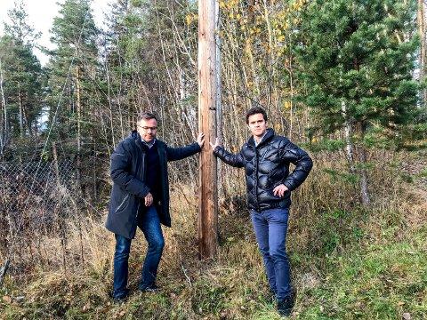 Står støtt: Njål Kjellesvik Norheim (t.v.) og Vegard Syvertsen med en av pålene som ble satt ned på dugnad.
