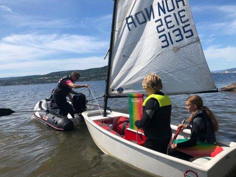 Mange barn koser seg på sommercamp. I seilbåten ser vi Felix Fønnebø og Inger Kristina Nielsen.