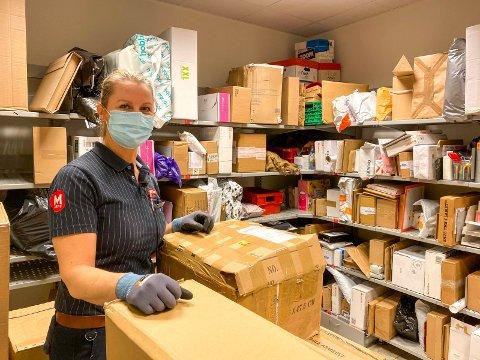VENTER: Kjøpmann på Meny på Liertoppen, Stine Ødegaard, har hyller fulle av pakker som venter på å bli hentet.