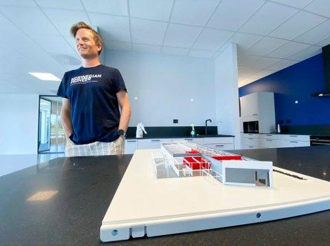 Torstein Myklebostad viser fram modellen for det nye  bygget han nå står inne i. Det er Veidekke som har vært entreprenør.