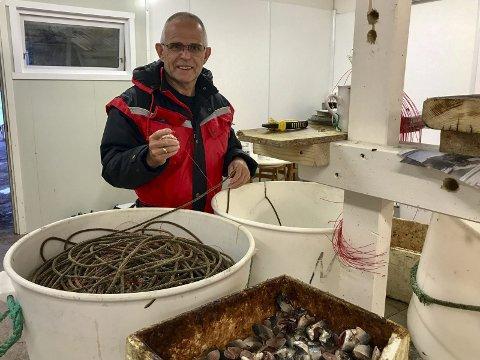 SESONGSTART: Kristian Gjertsen klargjør liner til blåkveitefiske. Han fester biter av sild på krokene, og legger avispapir mellom hver krok, for å unngå vas på lina.Foto: Kristian Johan Gjertsen