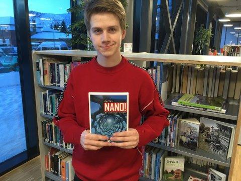 Elev Karl Lind (17) fra Svolvær har hentet bok om nanoteknologi på biblioteket i Svolvær for å lese seg opp før turen til Uppsala universitet.