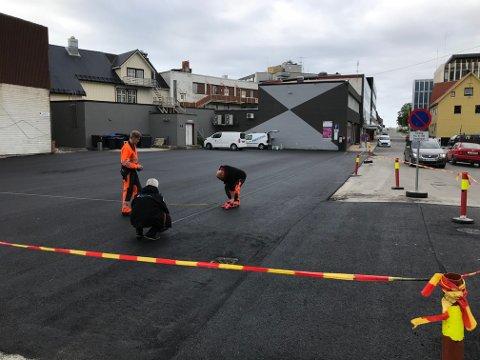 Kommunens parkeringsetat i ferd med fredag å måle opp det reasfalterte området i Storgata i Svolvær.