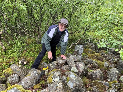 Menneskeskapt: Thor Erdahl er overbevist om at den trekantede steinformasjonen er menneskeskapt en gang i fortiden.  Her ved enden av trekanten som er markert med en slags liten bautastein. Foto: Hugo Johansen