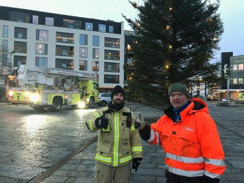 REPARERT: Rene Skjønnås (tv) i brannvesenet og Ørjan Karlsen i teknisk drift sørget fredag morgen for at lysene i julegranen på torget i Svolvær igjen var tente.