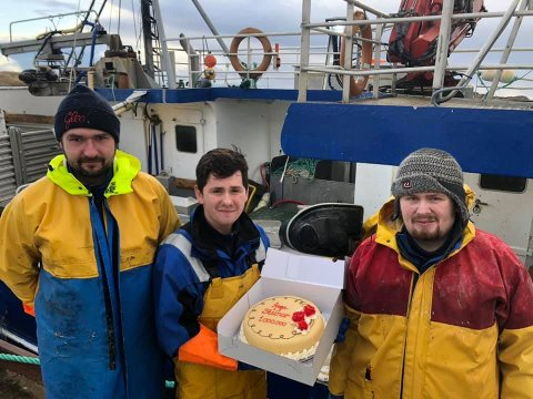 MILLIONKAKA: Nerius, Vegard og skipper Håvard(th) med årets første millionkake. Sander er også mannskap om bord, men var ikke tilstede da bildet ble tatt.