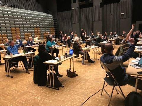 Avstemmingen i kommunestyret. De løftede hendene er stemmer for større basseng på Leknes, mot skolebassenger på Ballstad, Bøstad og i Stamsund.