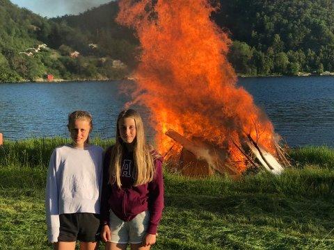 BÅL: Celine Bjelland Fredbo (til venstre) og Mariell Bjelland Fredbo foran det gedigne sankthansbålet på Kittelsnes.