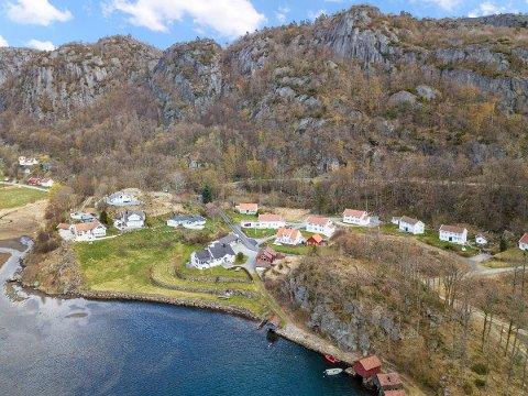 DYREST AKKURAT NÅ: Eiendommen omfatter det hvite huset midt på bildet, med fem mål tomt. Også den røde sjøbua nede til venstre hører med.