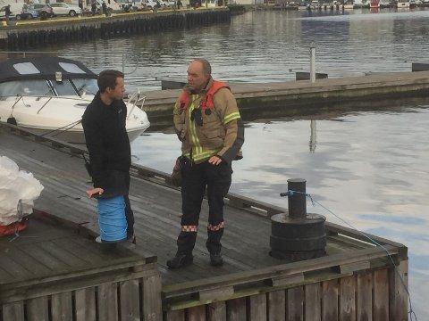 Brannkonstabel Michael Aspvik og brannmester Lars Micharlsen står ved Tollboden hvor de har lagt ut lenser.