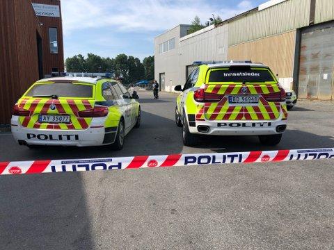 SPERRET AV: Fem politibiler og en rekke væpnede politifolk er på plass. Politiet jakter nå på tre menn etter at de skal ha truet en ansatt til å åpne en safe.