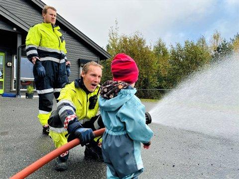 STOR STAS: Torsdag fikk Læringsverkstedet Våler Naturbarnehage besøk av brannvesenet i Moss. Her er det brannkonstabel Kyrre Larsen som viser hvordan man skal håndtere en brannslange. Brannkonstabel Carl-Fredrik Ockernahl følger nøye med på at alt går som det skal.