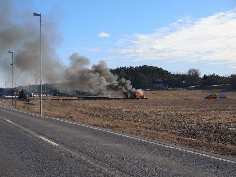 BRENNER: Bilen er i full fyr. Togtrafikken og veien har blitt stengt som følge av brannen.