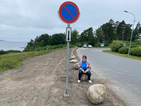 OPPRØRT: Kirsten Fredriksen Sæves (64) foran kampesteinene som er satt opp på strandpromenaden på Framnes, Jeløy: — Synes det er synd at man ikke kan parkere noen som helst sted på Jeløy, sier Kirsten opprørt.