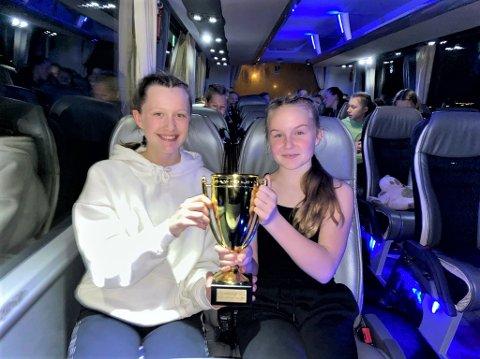 KM-POKALEN: Jenny Mårvik (til venstre) og Celine Hårstadstrand holder her pokalen som beviser at Gullvikmoen J14 er vinnerne av årets kretsmesterskap. Her i bussen på veg heim til NAmsos.