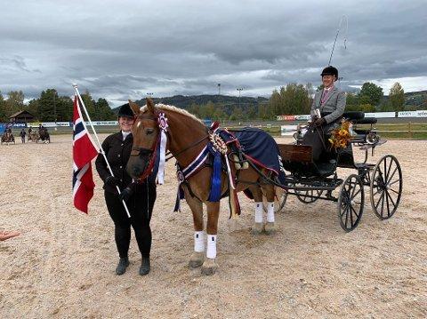 TIL TOPPS: Kusk Simon Lande fra Namsos og hans hest Dalbys Maisol avbildet under premieseremonien etter at NM-gullet var sikret. Til venstre: Tine Røste Haugen.