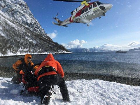 FLØYET UT: Alle de 12  involverte ble fløyet ned fra skredområdet med ambulansehelikopteret, og fraktet med båt ut til skipet (i bakgrunnen) hvor de bor for tiden.