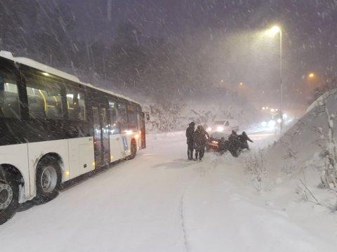 TRØBBEL: Her forsøker flere personer å hjelpe en personbil opp av grøfta i Tverrforbindelsen i Tromsø. Det er vanskelige kjøreforhold lørdag.