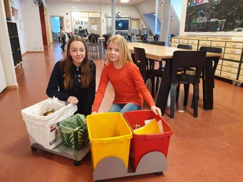 INGEN PLAST: Johanne Austad (13) og Smilla Glad Myrbakk (12) viser frem avfallsstativene som står rundt omkring på skolen. En dunk for papp. En for papir. En for matavfall og en for restavfall. Men ingen for plast.