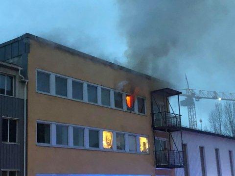 BRANN: Åpne flammer er synlige i fjerde etasje i bygningen hvor det brøt ut brann sent søndag kveld.
