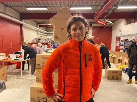 TRAVEL DAG: Her står Magnus Vold Jensen foran alle eskene som skal leveres ut. Bak ham suser de andre ansatte og frivillige rundt for å få pakket alt klart.