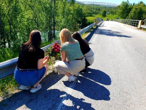 SØRGER: De tre unge kvinnene tenner lys og legger ned blomster ved Kistefossen. Foto: Øystein Barth-Heyerdahl