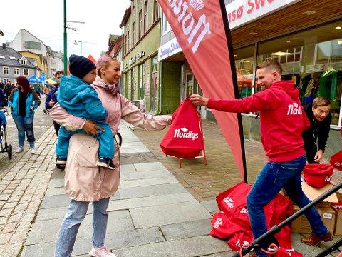LYKKETREFF: Aksel Fjelldal og mamma Helene Fjelldal hadde flaks med lykkehjulet, og fikk premie av sjefredaktør Helge Nitteberg under Nordlys' flyttefest i gågata lørdag.