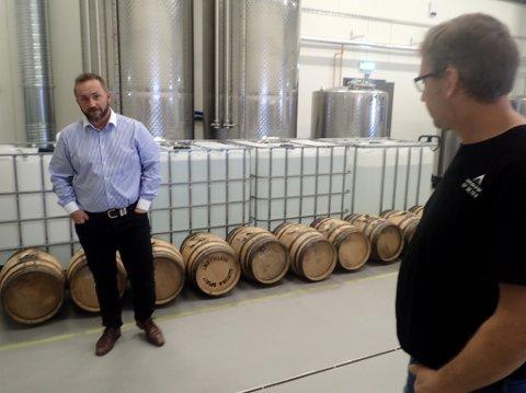 KJØPER NYE TØNNER: Tor-Petter W. Christensen foran ferdige tønner med gin. Bryggerimester Gjermund Stensrud er ansvarlig for produksjonen.