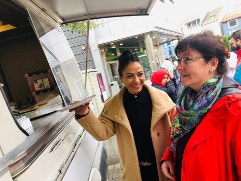 SMAKFULLT: Eliana Lakis og Solbjørg Hansen får en smakebit på festkaka som var med å markere åpningen av den nye matvogna Green Falafel på torget.