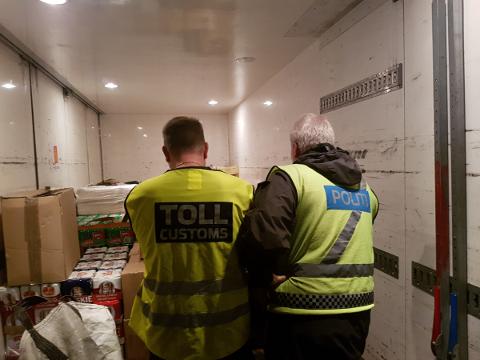 Mannskaper fra Ringsaker lensmannskontor og Åsnes tollkontor gjennomgår deler av det store beslaget av smuglervarer i Brumunddal.