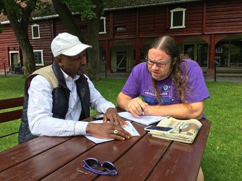 NYTTIG PRAT: Sudanske Youssef Mohammad får hjelp av NTNU-student Trond Viggo Ravnå til å forstå norske fakturaer.