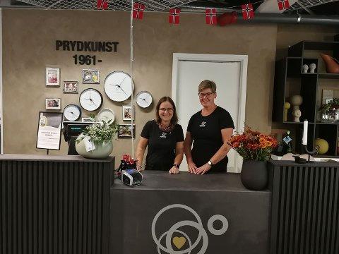 PRYDKUNST: Britt Holstad Torp og Hege Skumlien har hatt stor suksess i nye lokaler. I bakgrunnen ser vi deres tidslinje som går tilbake til da butikken åpnet i 1961.