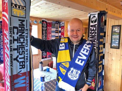 Torvild Sveen med supporter-skjerfene til favorittklubbene Biri IL og Everton FC over skuldrene i puben full at fotballeffekter hjemme i Biri Øverbygd.