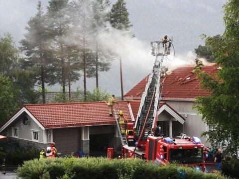 SLUKNINGSARBEID: I følge politiet skal brannen være i deler av huset. Slukningsarbeidet pågår.