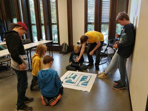 ROBOTKODING: Marius Stavik Eggen hjelper barna med å automatisere små roboter.