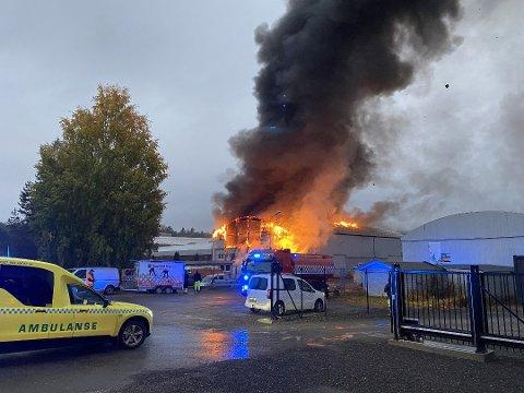 I FLAMMER: Flammene hadde onsdag morgen fått godt tak i næringsbygningen i Moelv.