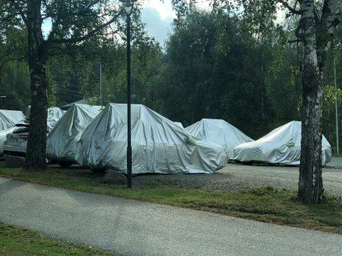 Hele 21 biler står parkert med sølvpresenninger over.
