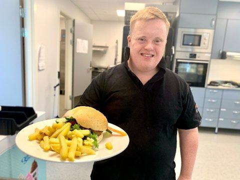 VÆRSÅGOD: Sigve Berge hadde en hektisk fredag. Her har han gjort klar burger og pommes frites til en sulten kafégjest.