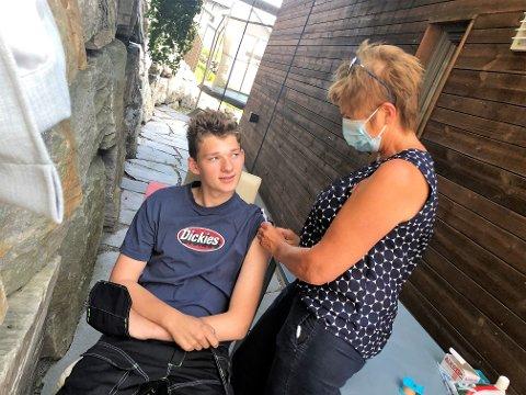 ET LITE STIKK: Jonas Leander Lokreim-Poulsson fikk sin første vaksine hjemme hos kommuneoverlegen. Selve stikket fikk han av vaksinekoordinator Borgny Hovi.