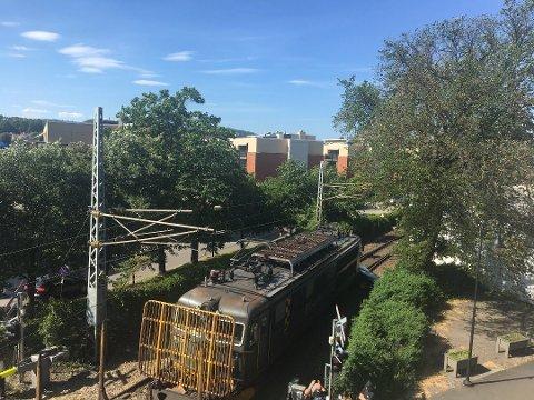 TOTALSKADET: Bilen ble skjøvet nærmere 50 meter nordover på toglinjen og nå jobbes det på spreng for å få den fjernet så Østfoldbanen kan åpne igjen.
