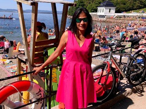 MANGE UTE I VANNET: President i Norges Livredningsselskap, Claire Ann Alfonso, på Hvervenbukta. Livredderen i bakgrunnen har blikket konstant festet ute i vannet.