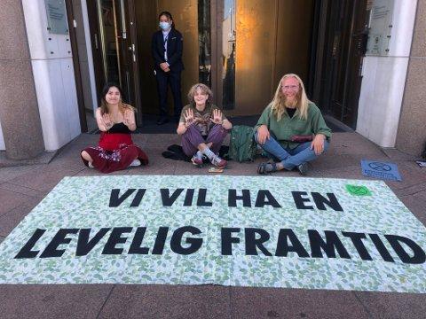 AKSJONERER: Cinta Hondsmerk (20) (f.v.), Karoline Hem Wiken (18) og Eskil Roll-Hansen (24) foran inngangen til Olje- og energidepartementet mandag. Aktivistene fra Extinction Rebellion mener sivil ulydighet er nødvendig for å få stanset norsk oljeleting.