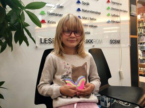 Eira Bjerk-Undrum koste seg på den nasjonale biblioteketsdagen på Larvik bibliotek. Her viser hun stolt frem sommerfuglen hun har perlet.
